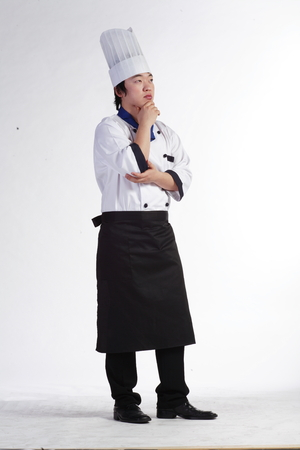 A male cook holding his chin thinking deeply