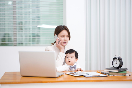 Foto per Working mom with the baby answering the phone at work - Immagine Royalty Free