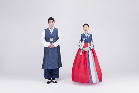 Photo for Young Asian couple in Hanbok, Korean traditional clothes, posing in the studio - isolated on white - Royalty Free Image