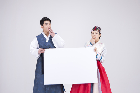 Photo for Young Asian couple in Hanbok, Korean traditional clothes, holding a blank board - isolated on white - Royalty Free Image