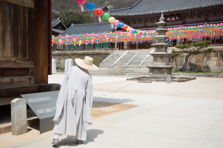 Buddhist temple in Korea - Monk wearing strat hat walking across the yard under the colorful lanterns