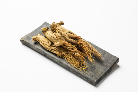 Photo for dried red ginseng,on korean traditional roof tile - isolated on white - Royalty Free Image