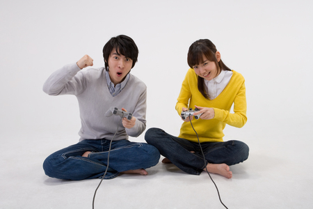 Asian teenager couple posing in a studio with game joysticks