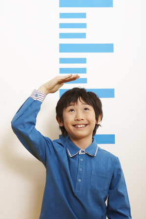 Foto de Young Asian boy measuring his height - Imagen libre de derechos
