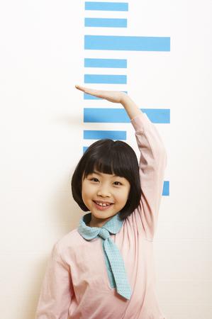 Photo pour Young Asian girl measuring her height - image libre de droit
