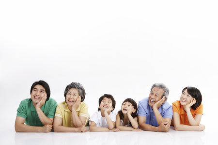 Photo for Three generations of Asian family posing in a studio lying on stomach - Royalty Free Image