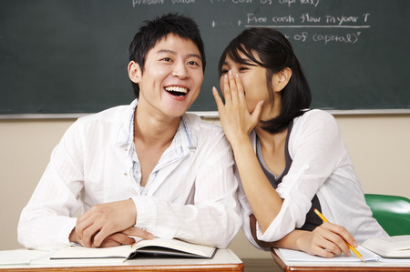 Asian college couple posing in a classroom as sitting at desk