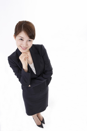 Asian business woman in suit posing in a studio with gesture