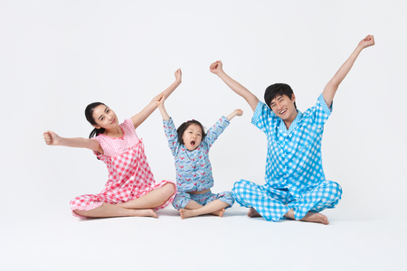 Parents and young kids spending family time together stretching in pajamas