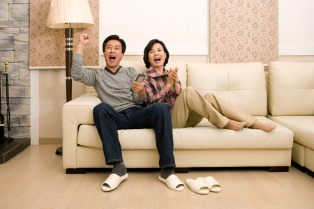 Foto de Mid-aged married Asian couple spending time together as watching TV in the living room - Imagen libre de derechos