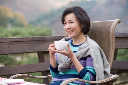Photo pour Mid-aged Asian woman posing as having coffee in the patio - image libre de droit