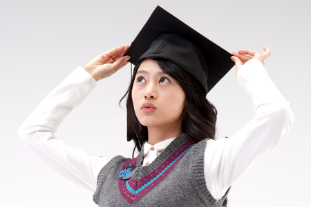 Close up Asian young woman with graduation cap isolated on white