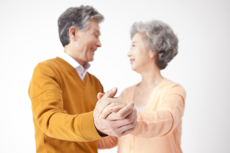 Asian old aged couple dancing isolated on white