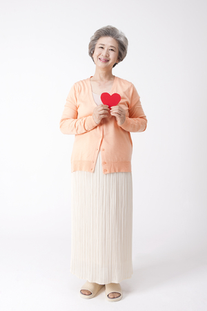 Foto de Asian old aged woman with heart paper isolated on white - Imagen libre de derechos