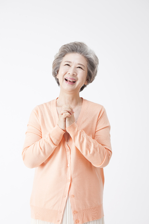 Foto de Asian old aged woman looking happy isolated on white - Imagen libre de derechos