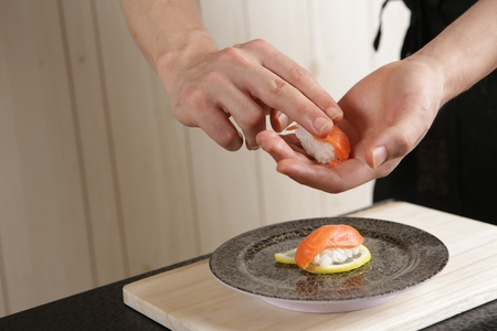 Chef's hand placing salmon sushi on a round plate