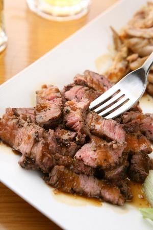 Forking up a chop steak from a rectangular plate
