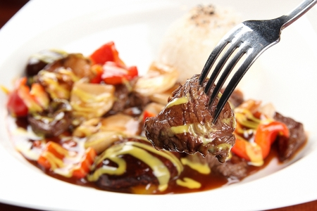 Forking up beef steak and vegetables stir-fried in teriyaki sauce, on round plate