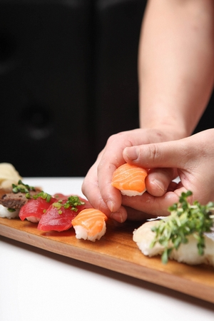 chef placing salmon sushi on assorted sushi board