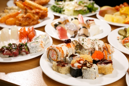 Foto de A table full of buffet food such as sushi, salad, boiled pork and fried pork cutlets, on white plates - Imagen libre de derechos