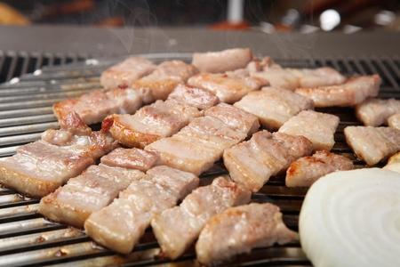 Foto de grilled onions and pork belly on grill - Imagen libre de derechos