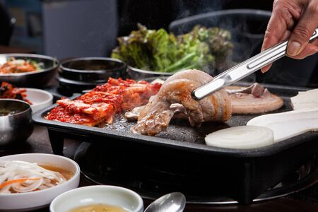 Photo for Pork belly being grilled on grill held by pincers - Royalty Free Image