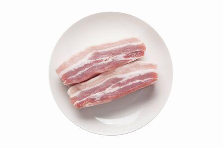 Foto de Raw pork belly served on wooden round plate in white - Imagen libre de derechos