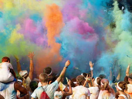 Color covered charity run finishers celebrate by throwing colored powder into air.