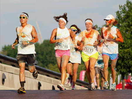 A mixed gender group of runners covered in colored powder participating in charity run.
