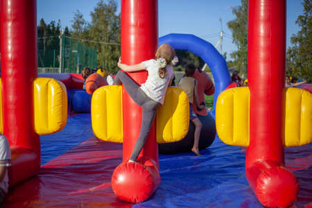 Photo pour Children frolic on trampolines. Inflatable play area for children. Fun in the park. A child jumps on a soft construction installed in the park. Holiday at the child. Holidays for the whole family. - image libre de droit