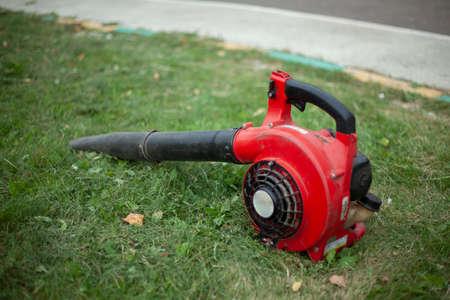 Foto de The garden vacuum cleaner lies on the grass. Blower for cleaning dry leaves. - Imagen libre de derechos