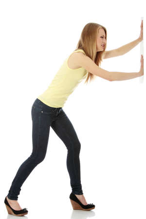 Woman pushing something imaginary isolated over a white background (white wall over her hands)