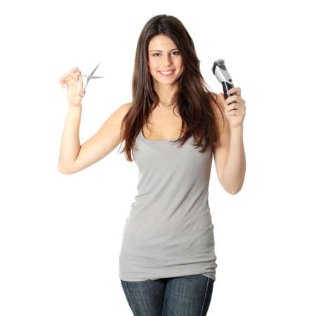 Young beautiful female hairdresser holding scissors and hair clipper, isolated on white