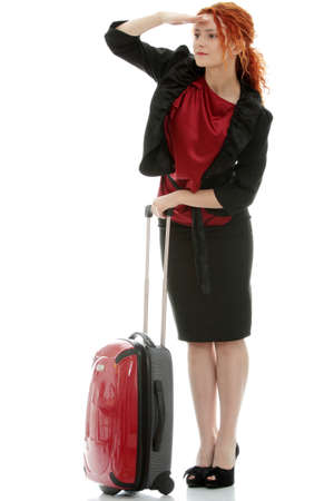 Young redhead businesswoman (deaf with hearing aid) with red suitcase, isolated on white backgroundの写真素材