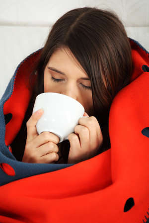 Photo for Young woman caught cold, wrapped up in blanket, drinking something hot from cup.  - Royalty Free Image