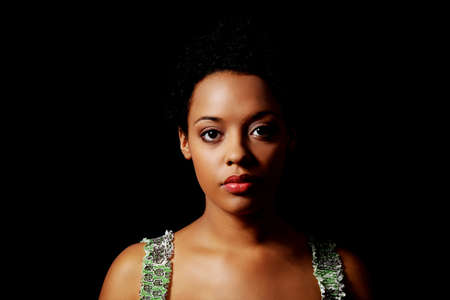 Portrait of beautiful serious afro american woman over black backgroundの写真素材