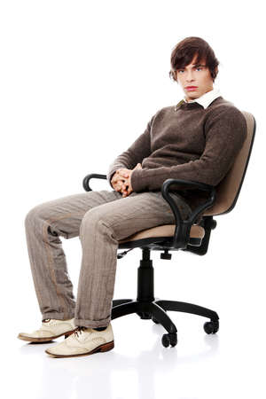 Young casual man on a chair, isolated on white