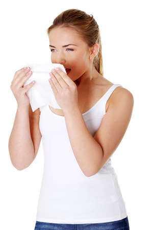 Young blonde girl sneezing and holding tissue.