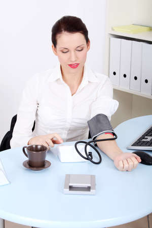 Beautiful caucasian businesswoman measuring her blood pressure in the office.