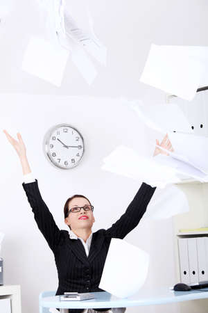 Pretty caucasian businesswoman throwing sheets of paper.
