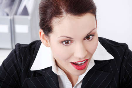 Face closeup of a beautiful business woman being positively surprised.