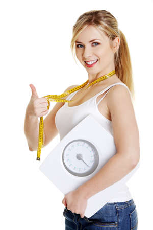 Foto de Woman with bathroom scale and measuring tape gesturing OK, isolated on white - Imagen libre de derechos