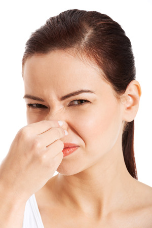 Portrait of a young woman holding her nose because of a bad smell  Isolated on white