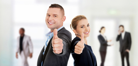 Foto de Happy business couple showing thumbs up. - Imagen libre de derechos
