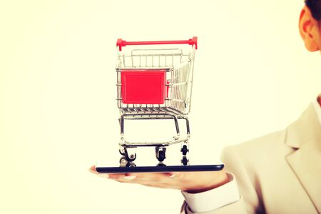 Photo pour African businesswoman with shopping cart and tablet. - image libre de droit