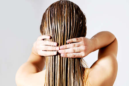 Photo pour Blond woman applying hair conditioner. Isolated on white. - image libre de droit