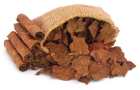 Photo pour Dry tobacco leaves in sack over white background - image libre de droit