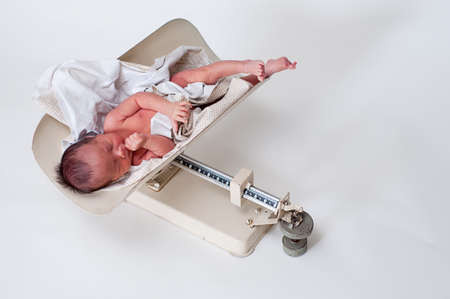 Neborn baby in a vintage scale being weighed