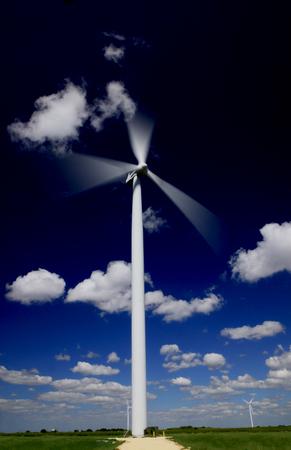 a hawt wind turbine in motion above an on land wind farm against a dark blue sky