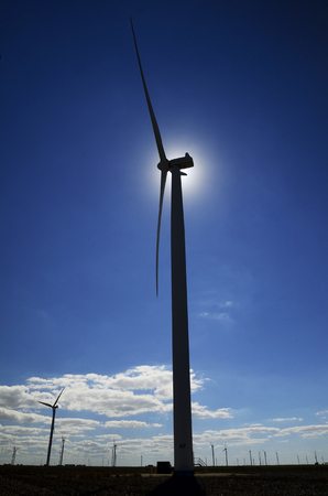 the silhouette of a hawt wind turbine stands still with the sun directly behind it's generator top